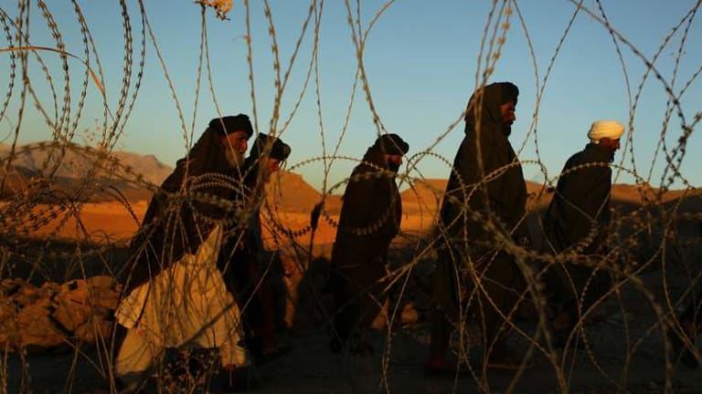 Kate Geraghty's winning entry for the news photograph of the year.  Pictured: A group of tribal elders walk past razorwire in the Uruzgan province in Afghanistan.