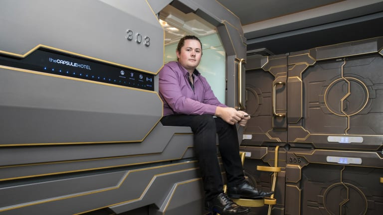 James Oliver, manager of the Capsule Hotel, sits in one of the capsules.