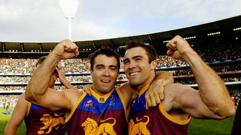 Chris Scott (L) and Brad Scott celebrate their 2002 Brisbane Lions premiership win.