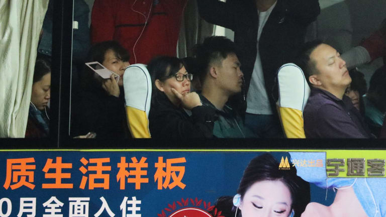 Commuters in Beijing during morning peak hour on board a bus emblazoned with property ads.