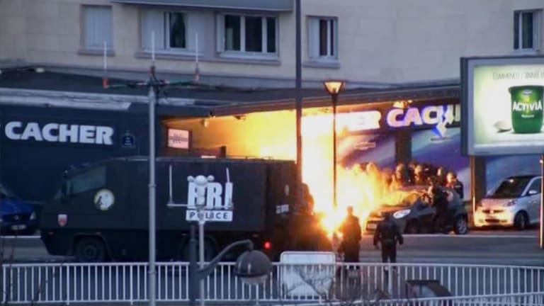 In this image taken from a video provided by PFMTV, police officers storm a kosher grocery to end a hostage situation in Paris.