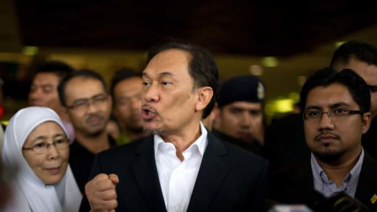 ''Politically motivated'' ... the Malaysian Opposition Leader, Anwar Ibrahim, puts his case outside court yesterday after being charged with violating a court order.