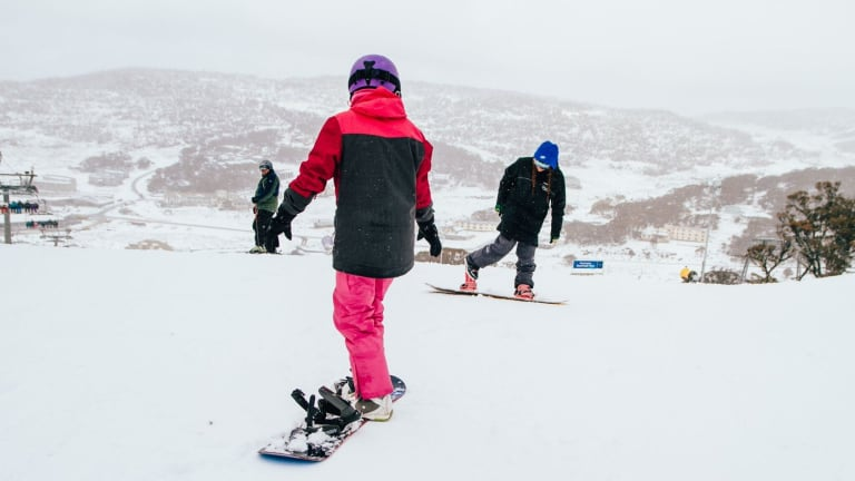 Some snowboarders at play during the snowfall at Perisher on Saturday.