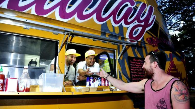Chris Baxter enjoys a meal from Andrew Hollands and Stewart Thaung, owners of the Mandalay Bus.