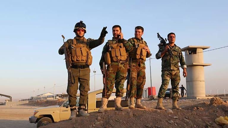 Kurdish Peshmerga fighters stand guard during airstrikes targeting Islamic State militants at the Khazer checkpoint outside of the city of Irbil in northern Iraq.