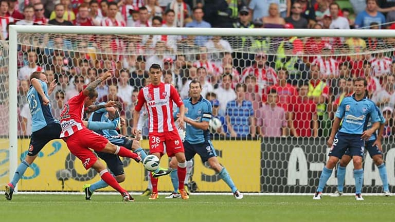 Neilly there: Melbourne's Nick Kalmar shoots to score the Heart's first goal as Sydney FC's Lucas Neill (right) watches on.