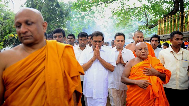 Mr Sirisena, centre, at a Buddhist temple in Kelaniya on Thursday.