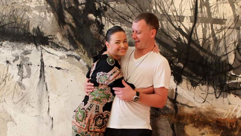 The price of love … Felicity Smith and Paul Lowe with the $12,000 Sophie Cape painting they are asking wedding guests to contribute towards.