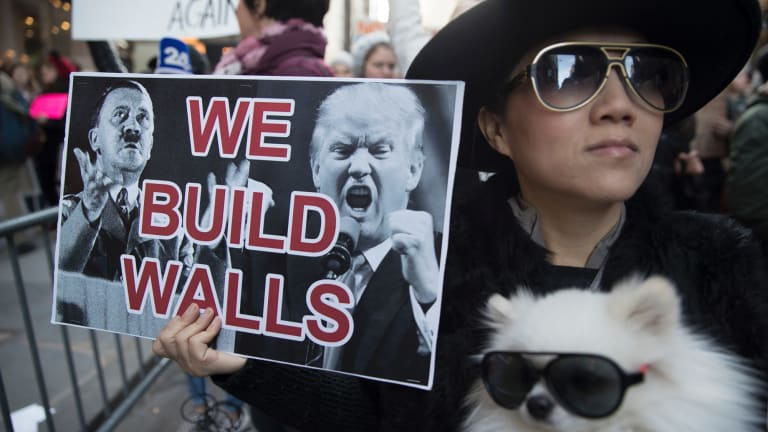 Chong Cha demonstrates against Donald Trump with her dog, Zuzu, outside Trump Tower on November 12.