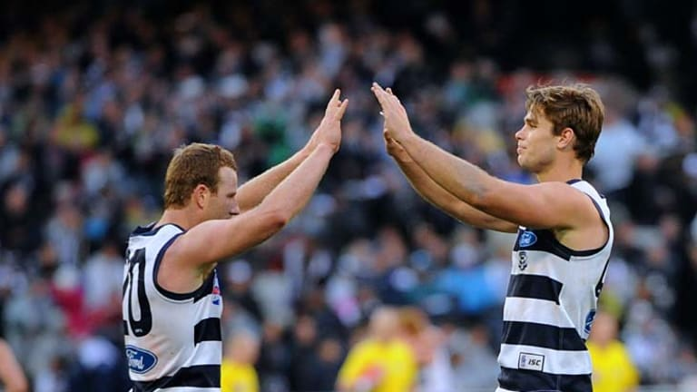 High fives: Steve Johnson (left) celebrates a goal he kicked after receiving a cheeky handball from Tom Hawkins.