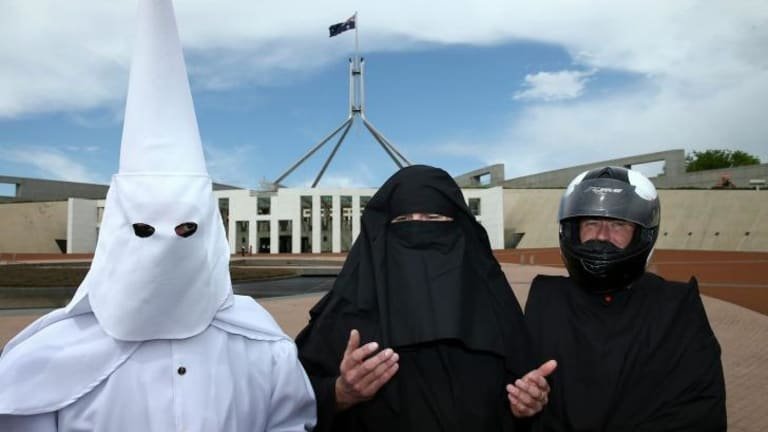 Three men cover their faces to protest the wearing of the burqa in public places.