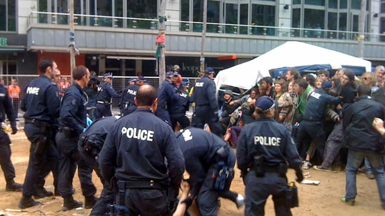 Police detain a man in City Square as other officers hold the crowd back.