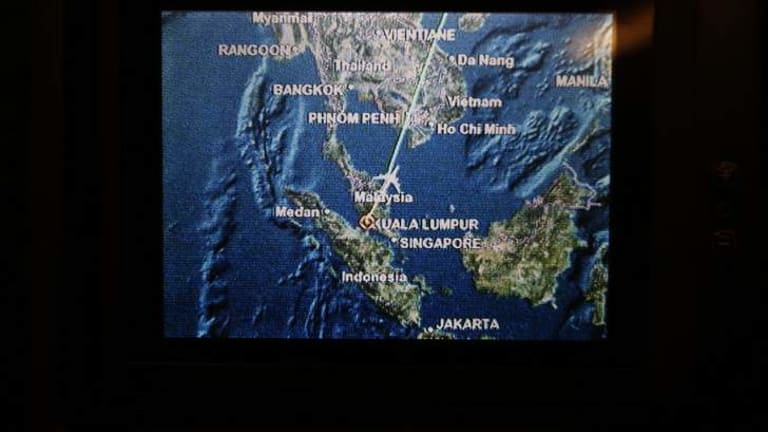 A screen on board Malaysia Airlines Boeing 777-200ER flight MH318 shows the plane's flight path as it cruises over the South China Sea from Kuala Lumpur towards Beijing, at approximately the same point when, on March 8, flight MH370 lost contact with air traffic controllers.