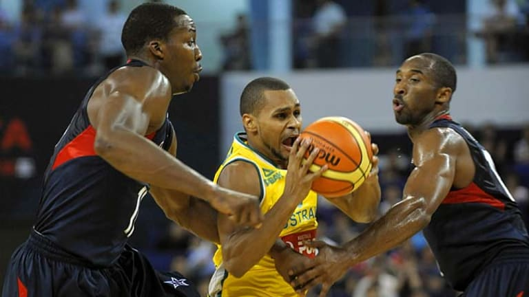 Patrick Mills (C) of Australia vies with Kobe Bryant (R) and Dwight Howard of the US.