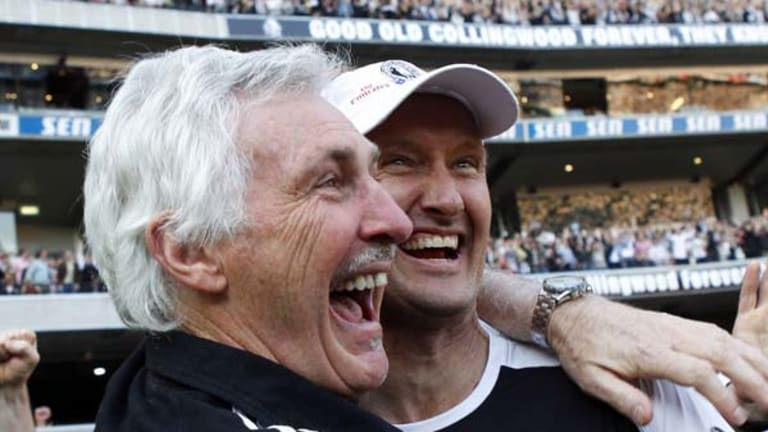 Mick Malthouse embraces fitness coach David Buttifant after the win.