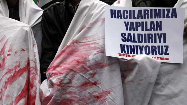 Syrian protesters in Turkey call for action against Bashar al-Assad, some dressed in shrouds stained with mock blood.