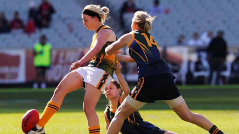 Lauren Arnell gets a kick away as Kiara Bowers and Monica O'Brien (No. 14) try for the tackle at the MCG in the Green All Stars versus Brilliant Gold from the AFL women's high performance academy.
