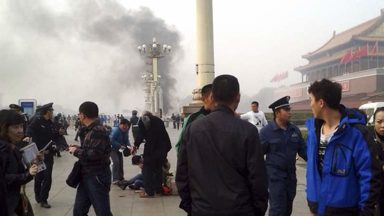 People watch from nearby Chang'an Avenue as smoke rises in front of the Tiananmen Gate on Monday.