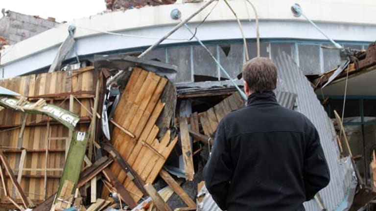 New Zealand Prime Minister John Key stands in front of a destroyed building in Kaiapoi.