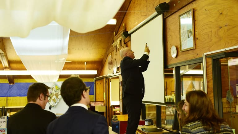 Adrian Piccoli photographs a story on a library wall about David Gonski's visit to Villawood North Public School. The issue of Gonski funding is on the education agenda.
