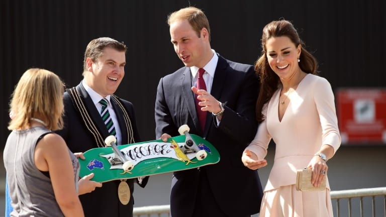 City of Playford Mayor, Mr Glenn Docherty, presents a skateboard to Prince William and Catherine at a skate park in Elizabeth on Wednesday.