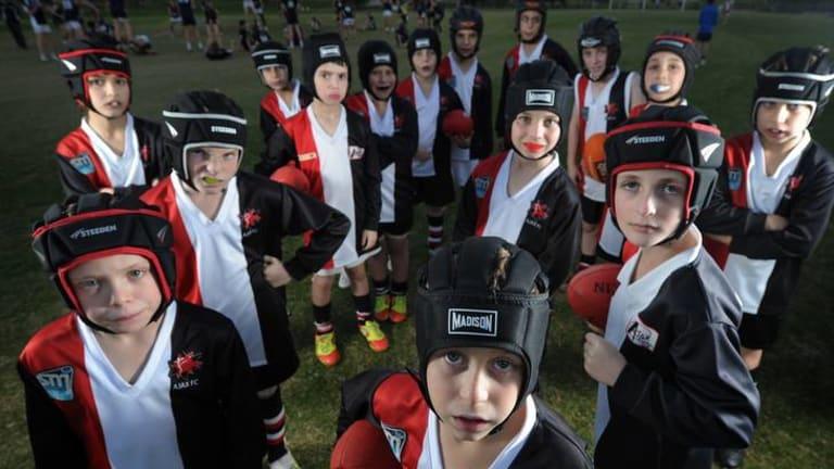 Children at Caulfield's Ajax junior football club wear helmets.