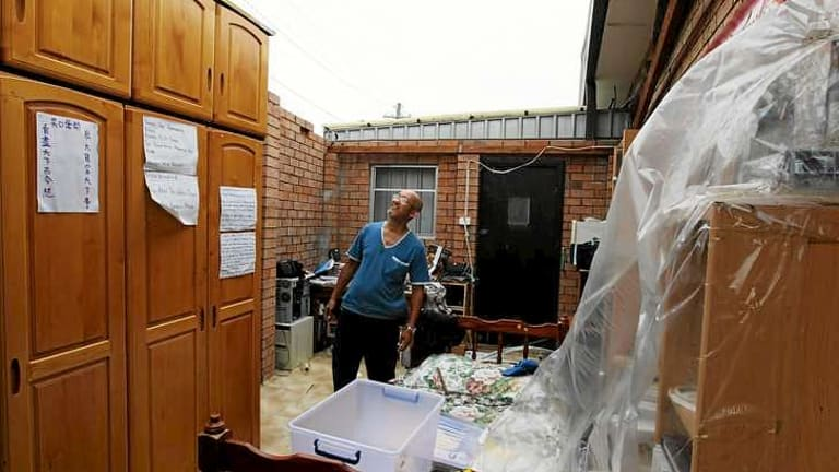 Chifley resident Harry Tran, pictured in one of the rooms in his house that lost its roof.