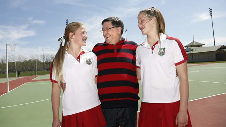 Former chief of staff to John Howard and now Federal Director of Barton Deakin Government Relations Grahame Morris, centre, with his twin daughters Genevieve Morris, left, and Hayley Morris , right, before they play in their school netball grand final at the Deakin Netball Courts in Canberra.