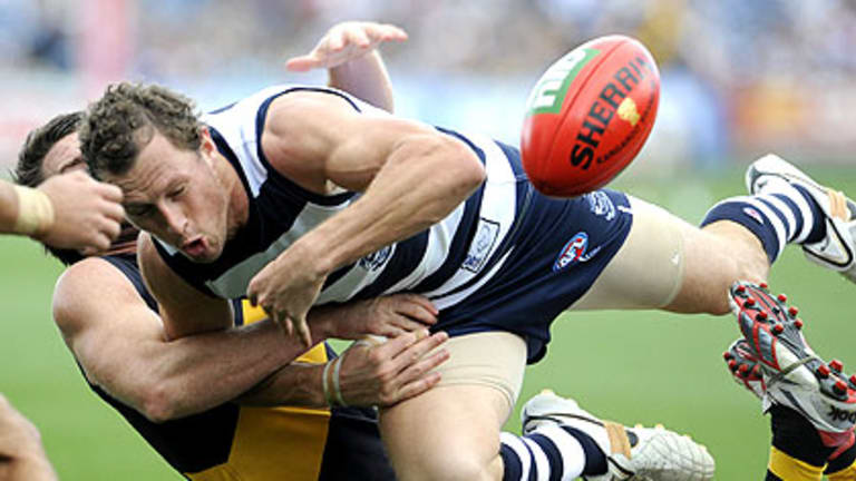 Geelong's James Kelly loses the ball as he tries to crash through a Chris Newman tackle at Skilled Stadium yesterday.