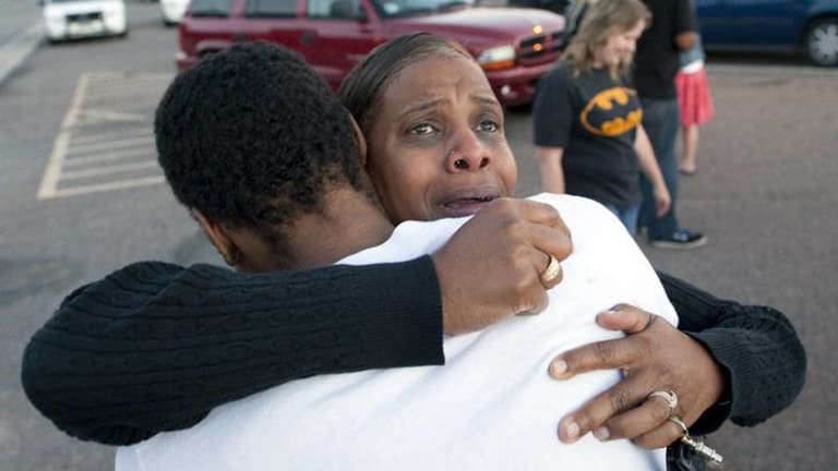 Shamecca Davis hugs her son Isaiah Bow, who was a witness to the shooting, outside Gateway High School where film-goers were brought for questioning.