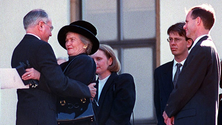 Then prime minister John Howard hugs then senator Jocelyn Newman at the funeral for her husband Kevin, while Campbell Newman (far right) looks on.
