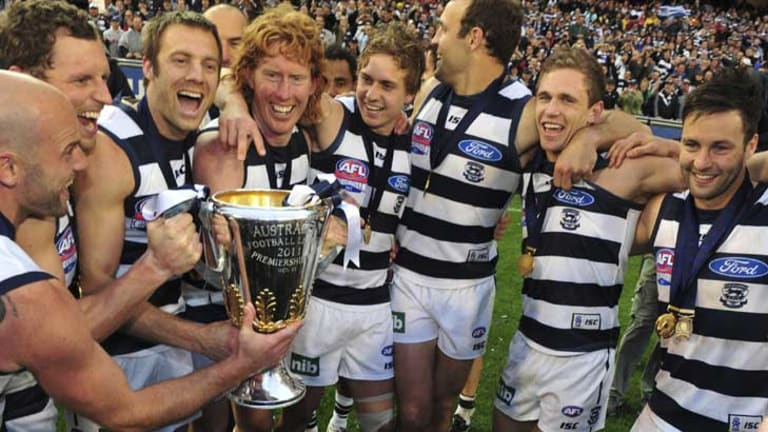 Geelong players soak up their premiership win.