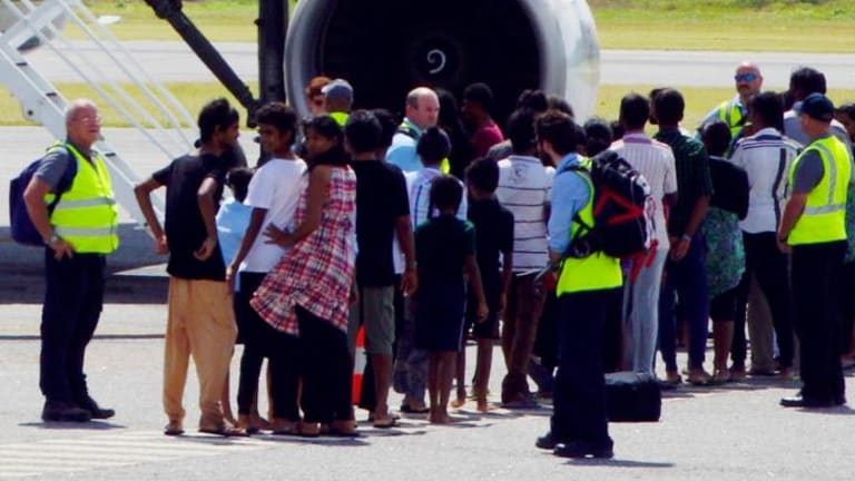 Plight of Tamils: A group of asylum seekers get on board an airplane at Cocos Island on Sunday, July 27, en route to Curtin detention centre in Western Australia.