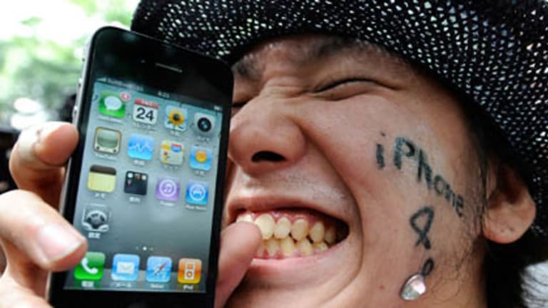 A man holds his iPhone 4 in front of a mobile phone store in Tokyo.