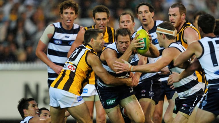 Tough Cat: Joel Corey bursts through Hawk Chance Bateman's tackle as Joel Selwood moves in to assist at the MCG yesterday.
