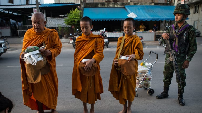 Buddhist Monks are guarded by Thai soldiers on their morning rounds collecting alms in Pattani.