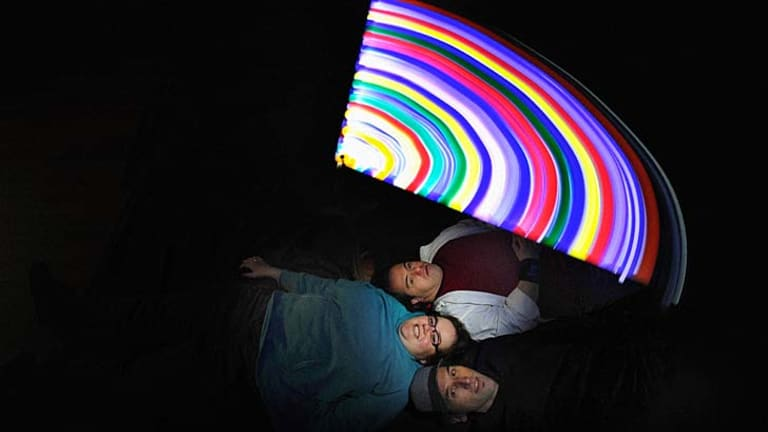 Lightening up: Lindsay Cox (bottom), Alisha and Capo in a spin with their art installation.