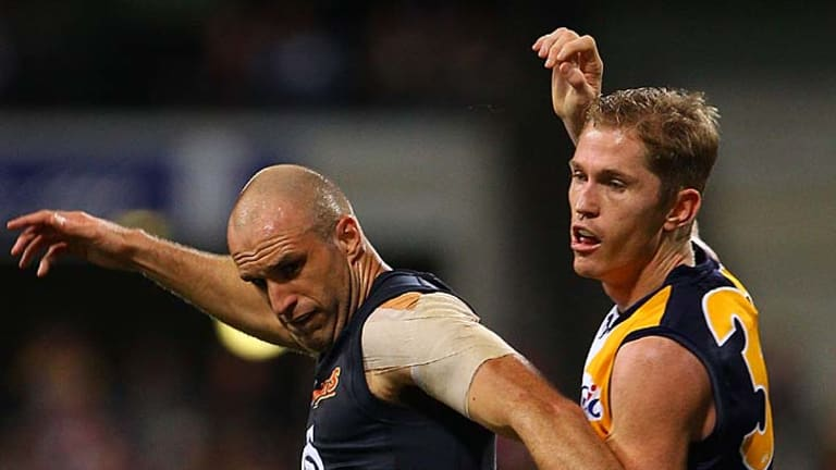 Adam Selwood and Chris Judd contest the ball during the first semi-final.