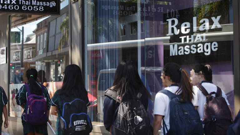 Schoolchildren walk past the Relax Thai Massage parlour at Crows Nest.