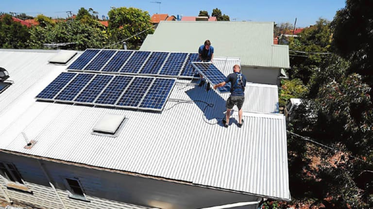 Peter Allan (top) removes solar panels from his Brunswick house in frustration at Government policies.