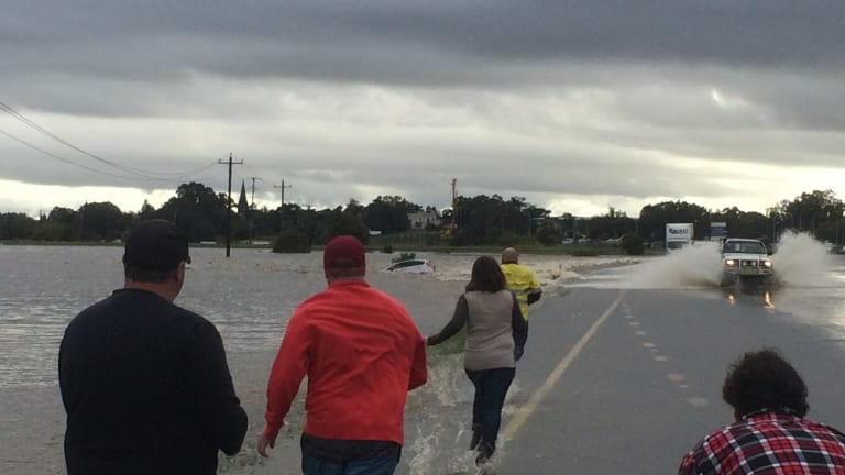 Rescuers rush to a car that is stranded in flood waters in Maitland.