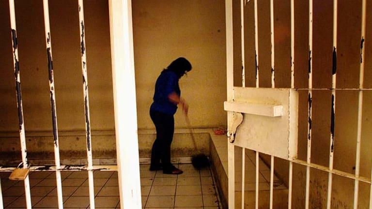 A woman cleans the holding cell at the Denpasar courthouse.