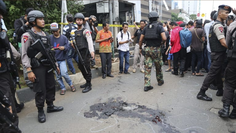 Police officers push back curious onlookers from the spot near a police post where an explosion went off in Jakarta.