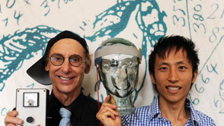 """Professor Allan Snyder, left, and PhD student Richard Chi, right, display their """"thinking cap"""" on a glass head at the University of Sydney."""