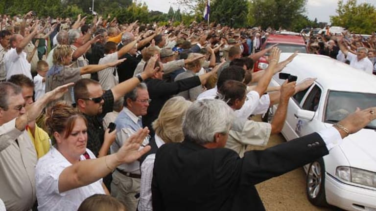 Supporters of slain white supremacist leader Eugene Terreblanche, give a Nazi-style salute to his coffin as it is driven from the church in Ventersdorp, South Africa.