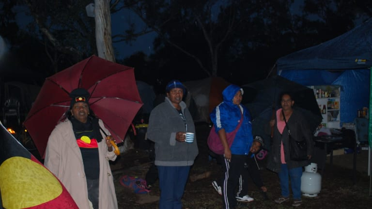 Protesters look on after police storm the camp site on Heirisson Island