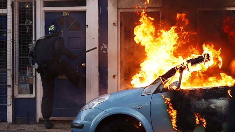 A riot police officer attempts to break down the door of a house next to a burning car in Clarence Road in Hackney.