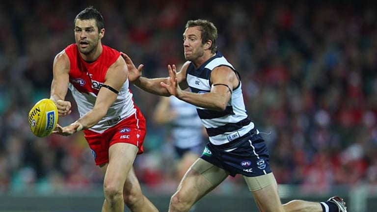 Swan Heath Grundy evades a tackle by Cat Joel Corey.