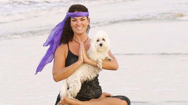 Doga instructor Suzi Teitelman and dog Roxy  in a cross-legged pose at Ponte Vedra Beach, Florida.