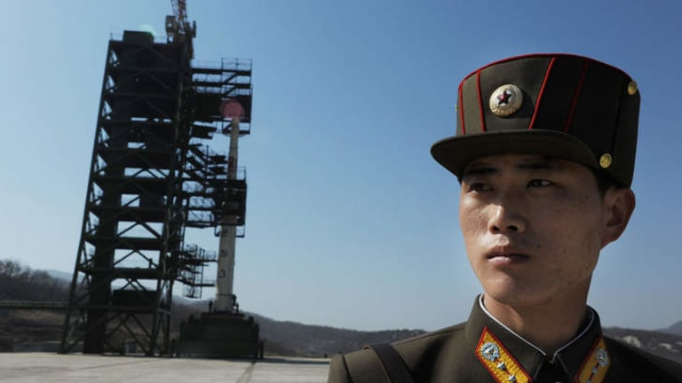 Missile controversy... a North Korean soldier stands guard in front of an Unha-3 rocket at Tangachai -ri space centre in April.